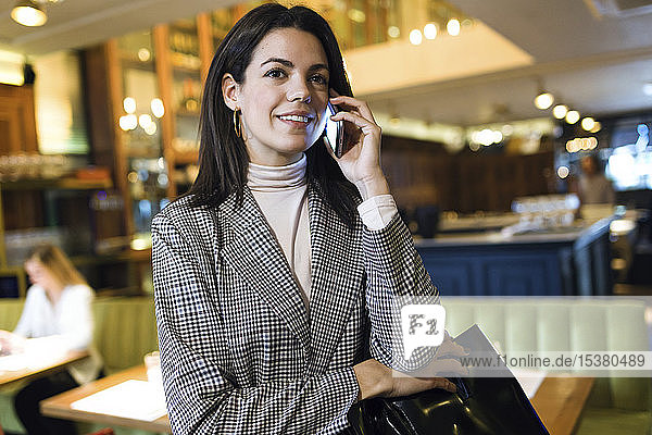 Businesswoman talking on cell phone in a restaurant