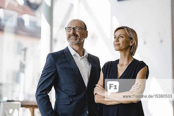 Porträt eines selbstbewussten Geschäftsmannes und einer selbstbewussten Geschäftsfrau