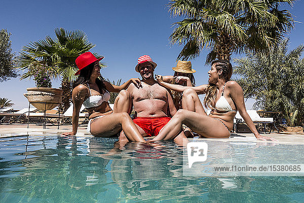 Overweight man surrounded by affectionate beautiful women at the poolside