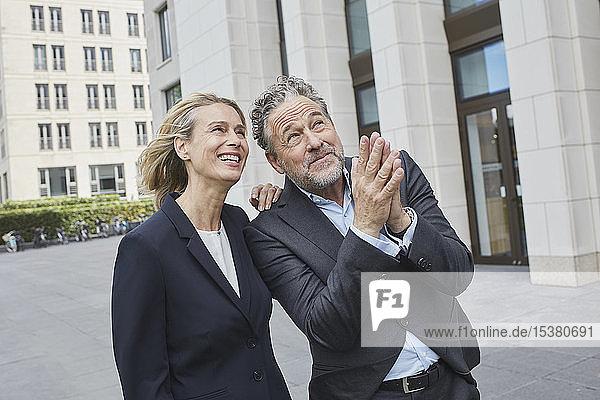 Glücklicher Geschäftsmann und glückliche Geschäftsfrau in der Stadt blicken auf