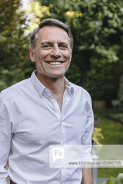 Portrait of a mature smiling man in the garden