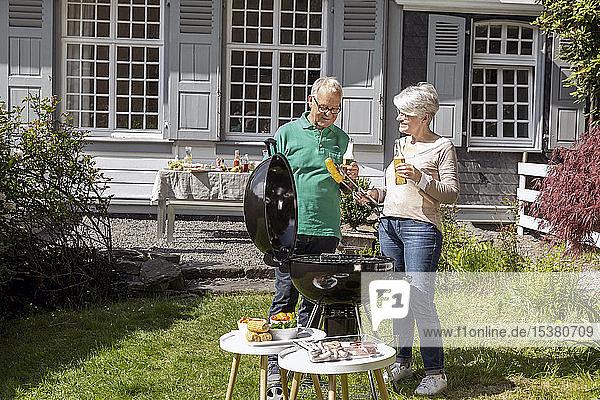 Glückliches älteres Ehepaar beim Grillen im Garten ihres Hauses
