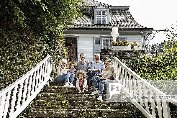 Glückliche Großfamilie  die auf einer Treppe im Garten ihres Hauses sitzt