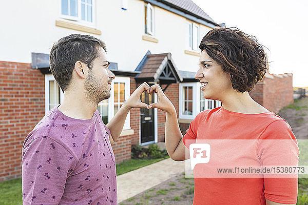 Glückliches Paar formt ein Herz mit Händen vor ihrem neuen Zuhause
