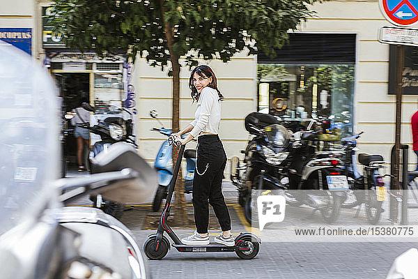 Junge Frau mit E-Scooter in der Stadt