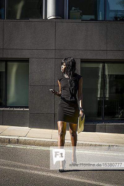 Geschäftsfrau überquert Straße und hält Smartphone in der Stadt