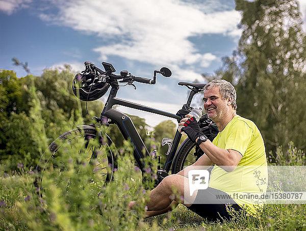 Happy mature man taking a break during his bike tour with an e-bike