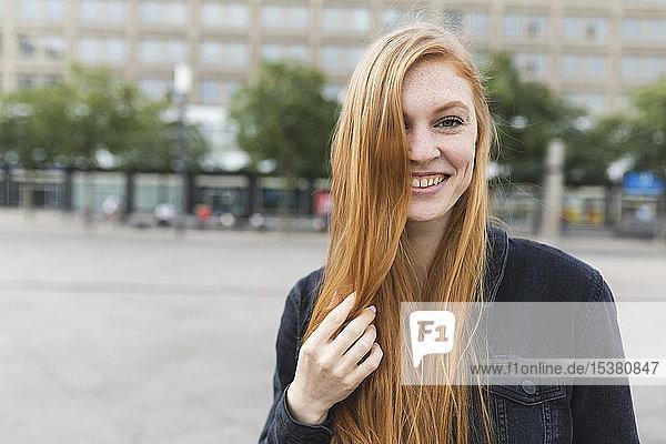 Porträt einer rothaarigen jungen Frau auf dem Alexanderplatz  Berlin  Deutschland