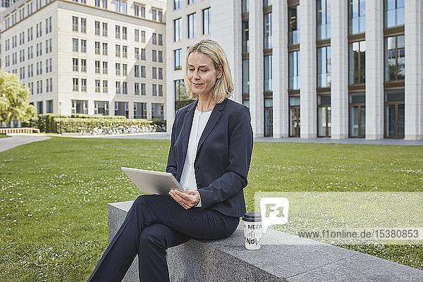 Geschäftsfrau sitzt in der Stadt mit Tablette an einer Wand