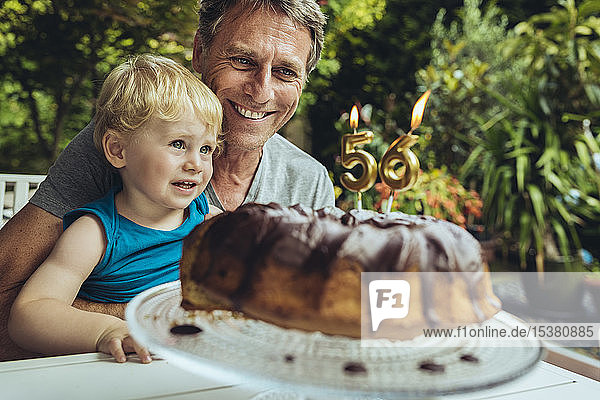 Little boy sitting on lap of father,  celebrating his birthday