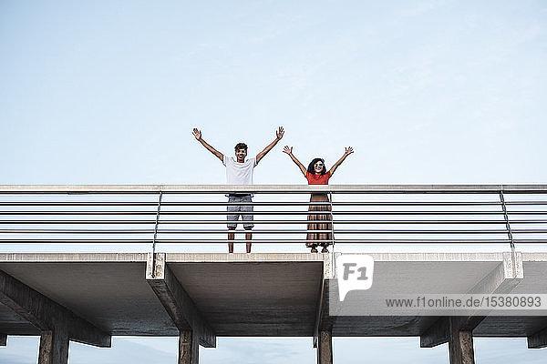Junges Paar steht auf der Brücke und winkt mit erhobenen Armen Junges Paar steht auf der Brücke und winkt mit erhobenen Armen