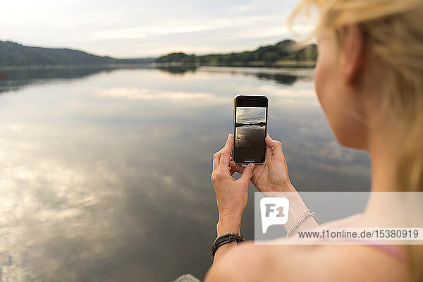Young woman taking a smartpgone picture at a lake