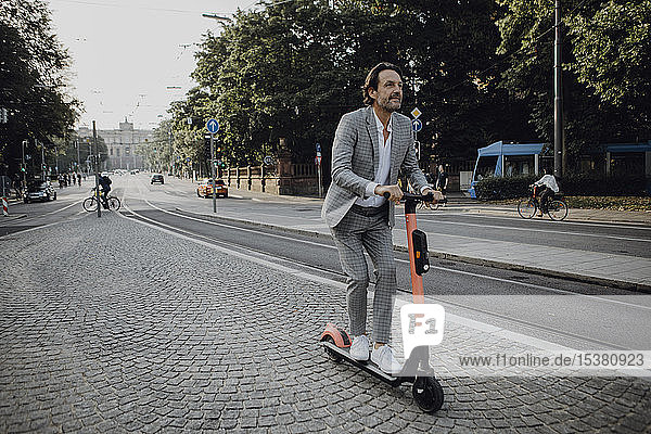Businessman with e-scooter in the city