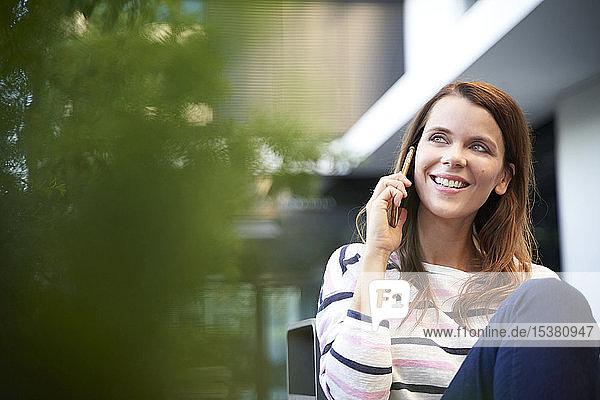 Lächelnde Frau beim Telefonieren in der Stadt