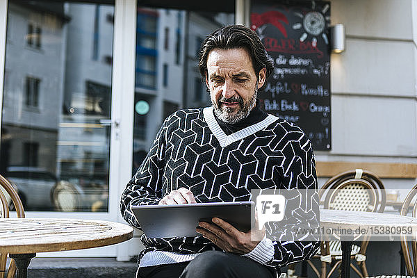 Portrait of fashionable mature man using digital tablet at pavement cafe