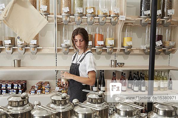 Junge Frau beim Einkaufen im verpackungsfreien Supermarkt Junge Frau beim Einkaufen im verpackungsfreien Supermarkt