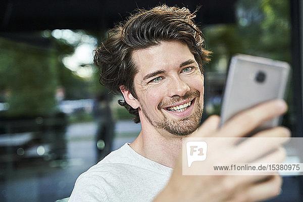 Porträt eines glücklichen Mannes mit Handy in der Hand in der Stadt
