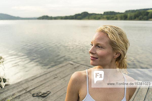Junge Frau auf einem Steg an einem See  die wegschaut