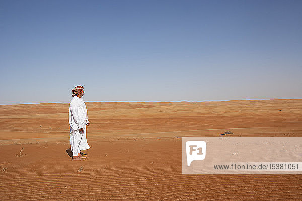 Beduine in Nationaltracht in der Wüste stehend,  Rückansicht,  Wahiba Sands,  Oman