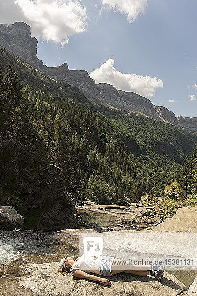 Woman lying on a rock in the mountains  Ordesa national park  Aragon  Spain