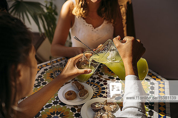Woman serving lemonade to her friend in a Moroccan cafe