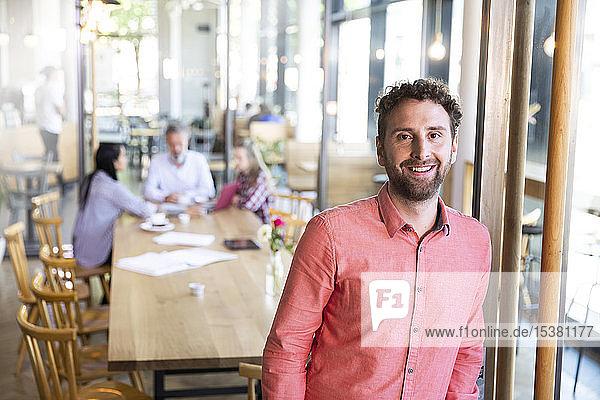 Porträt eines Gelegenheits-Geschäftsmannes in einem Cafe mit Kollegen  die im Hintergrund ein Treffen haben