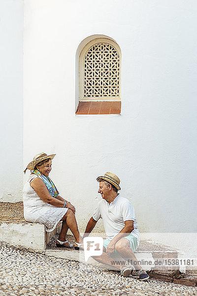 Glückliches älteres Touristenpaar  das auf Stufen in einem Dorf sitzt  El Roc de Sant Gaieta  Spanien