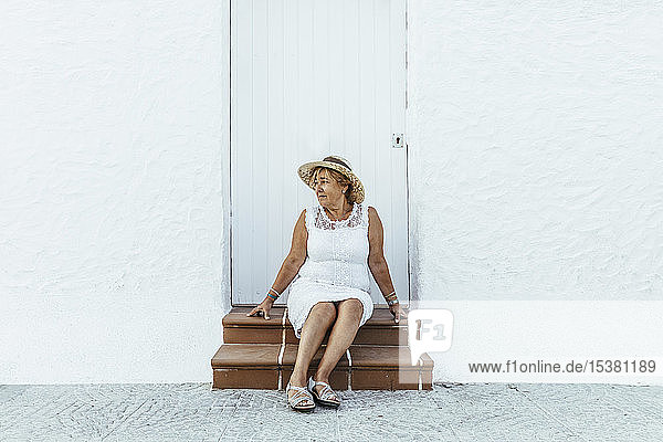 Älterer Tourist sitzt in einem Dorf auf der Treppe  El Roc de Sant Gaieta  Spanien