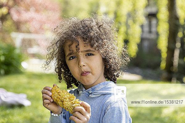 Porträt eines Jungen  der im Garten einen Maiskolben isst