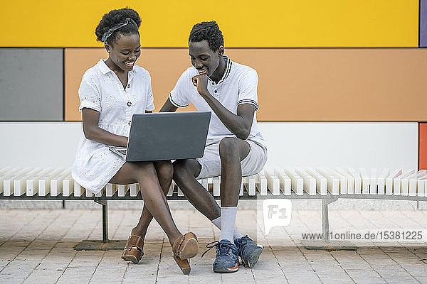Lächelndes junges Paar sitzt auf der Bank und schaut auf den Laptop