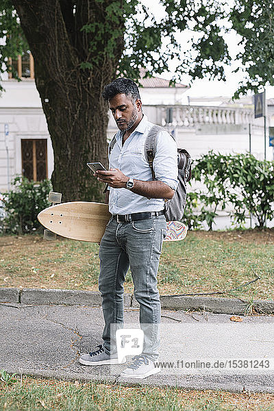 Casual businessman with skateboard using smartphone in the city