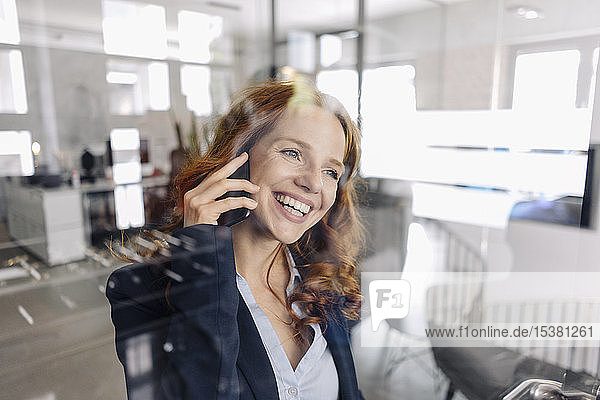 Happy redheaded businesswoman on the phone in office