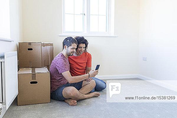 Glückliches Paar sitzt in neuer Wohnung auf dem Boden und benutzt ein Handy