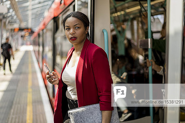 Portrait of businesswoman with cell phone getting out off the train  London  UK