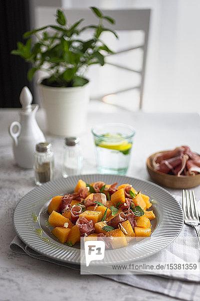 Hochwinkelansicht eines Melonensalats  der in einem Teller auf dem Tisch serviert wird