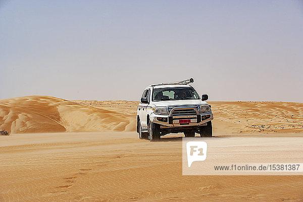 Tourist fährt in der Wüste im Geländewagen  Wahiba Sands  Oman