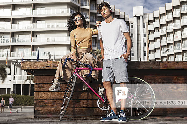 Cool couple with bicycle in the city
