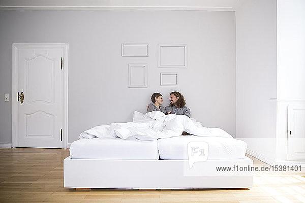 Glückliches junges Paar zu Hause im Bett