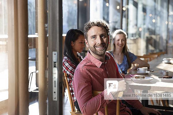 Porträt eines lächelnden Mannes mit Freunden in einem Cafe