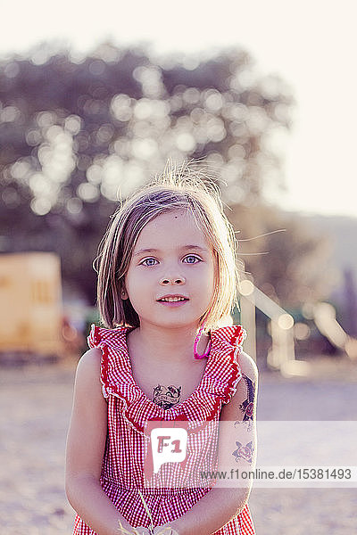 Portrait of little girl with temporary tattoos at sunset