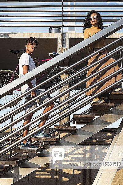Junges Paar beim Treppensteigen  Fahrrad tragend