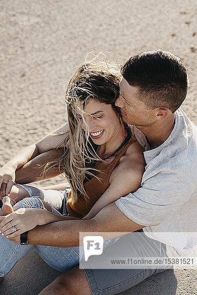 Glückliches  anhängliches junges Paar sitzt am Strand