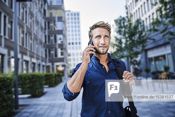 Confident young businessman on the phone in the city