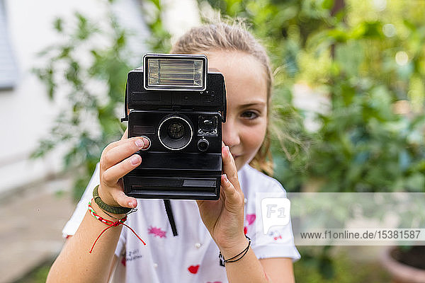 Girl taking a picture with an old-fashioned camera outdoors