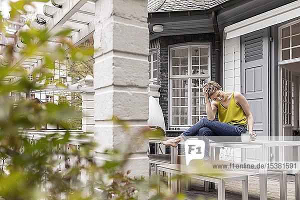 Entspannte Frau sitzt auf dem Terrassentisch im Garten ihres Hauses
