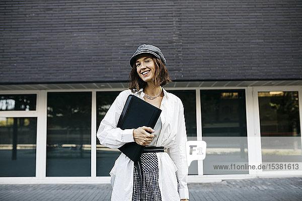 Hübsche Frau  Ordner tragend  in der Stadt pendelnd