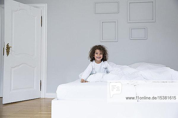 Porträt eines süßen  glücklichen Jungen im Bett