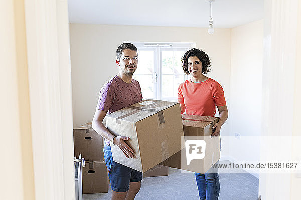 Portrait of happy couple moving into new home carrying cardboard boxes
