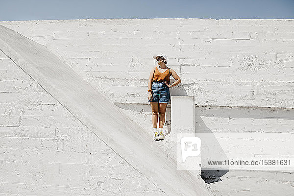 Young woman standing in front of a white wall outdoors