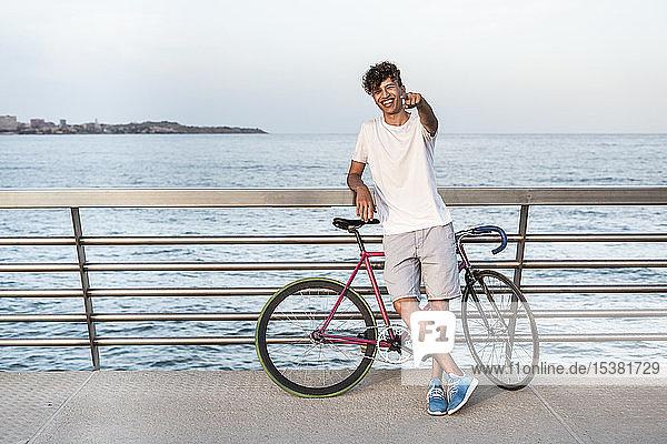 Junger Mann mit Fahrrad  auf der Brücke am Meer stehend Junger Mann mit Fahrrad, auf der Brücke am Meer stehend